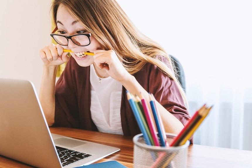 Eine gestresste Frau sitzt am Schreibtisch.