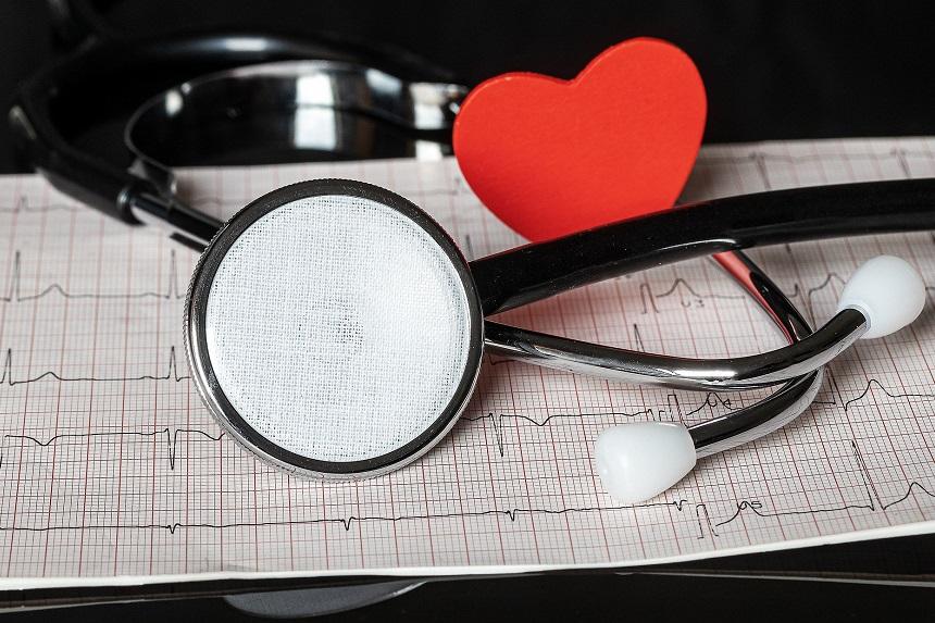 Ein Stethoskop liegt zusammen mit einem Herz auf einem Tisch.